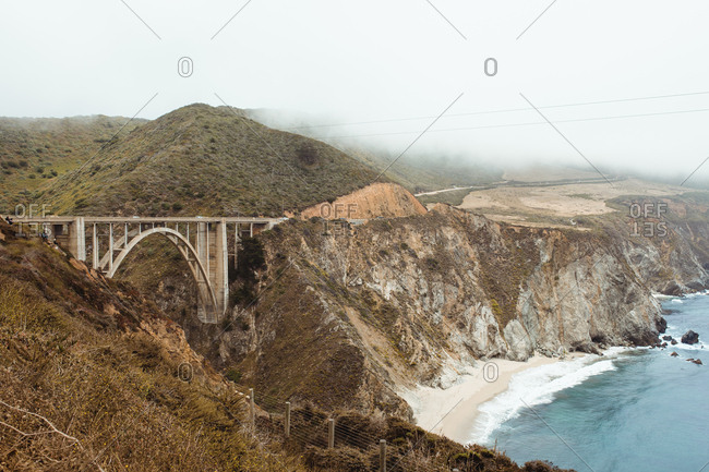 Empty stony rocky shore and bridge and clean blue water under light cloudy sky in Big Sur