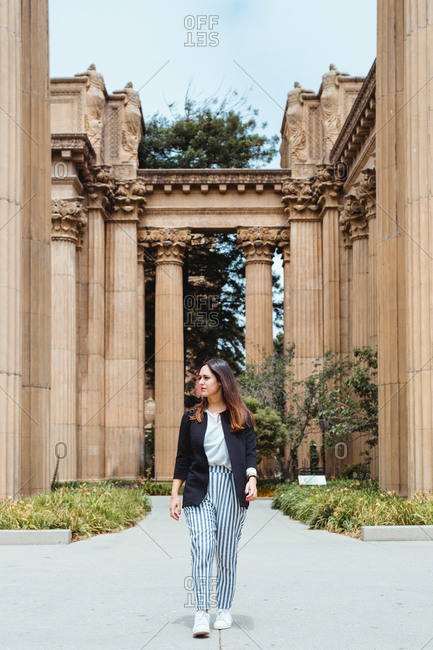 Curious woman walking on pavement between tall massive columns and looking around in San Francisco