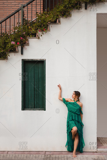Full body barefoot female in green dress leaning on white wall of house with staircase and potted flowers on town street
