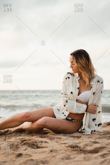Woman resting on sandy beach on cloudy day