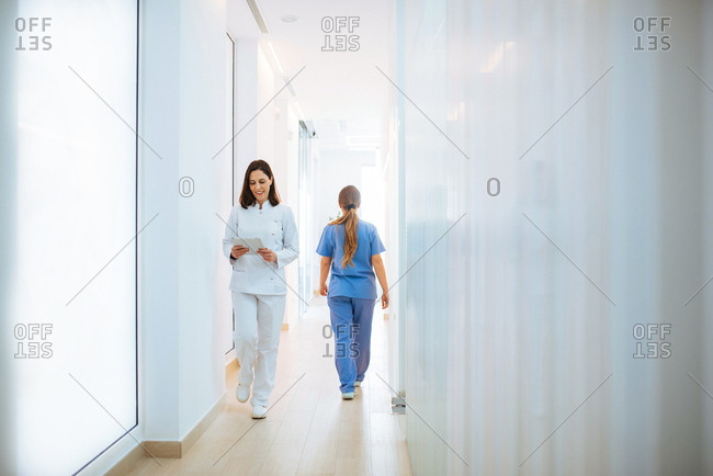 Cheerful doctor in white uniform reading document while walking along light corridor in clinic