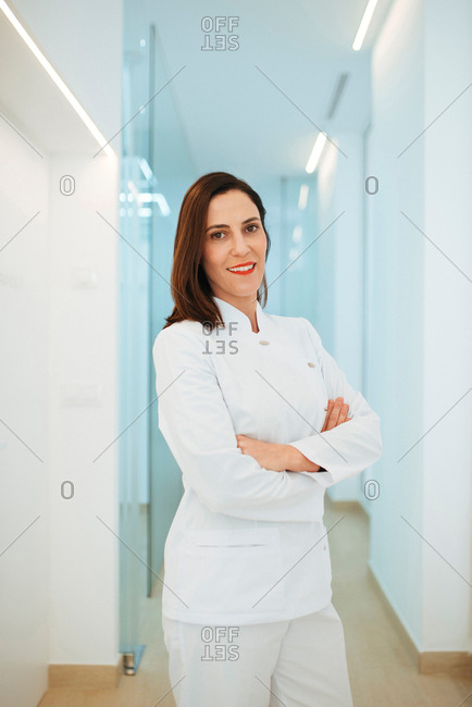 Cheerful elegant doctor in white uniform smiling at camera with crossed arms in light corridor