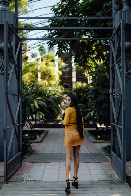 Back view of fashion trendy Asian woman with long dark hair in yellow short dress walking along metal decorative fence and looking at camera over shoulder