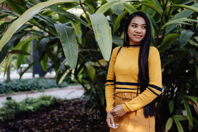 Side view of trendy Asian woman with long dark hair in yellow shirt and short skirt standing in beautiful garden and looking away