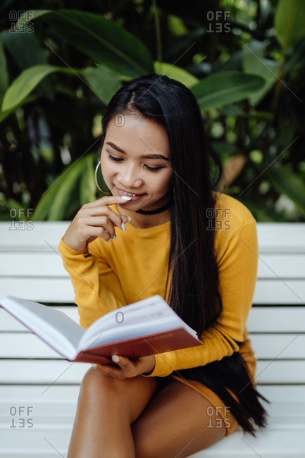 Side view of smart brunette Asian woman reading book in red cover sitting on white bench in park