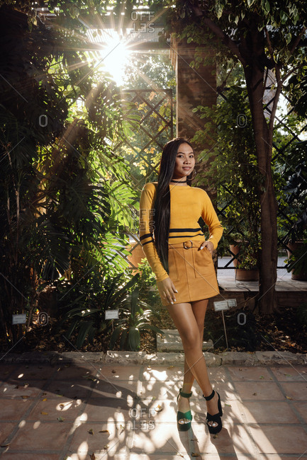 Side view of trendy Asian woman with long dark hair in yellow shirt and short skirt standing in beautiful garden and looking at camera