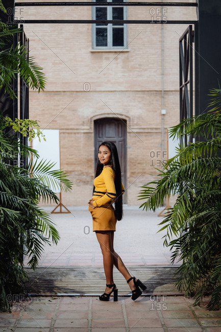 Side view of stylish trendy Asian woman with long dark hair in yellow short dress posing under decorative metal arch and looking at camera on background of building