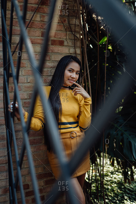 Charming fashion trendy Asian woman with long dark hair in yellow turtleneck and short skirt leaning on bricked wall holding metal fence and touching lips while mysteriously looking at camera