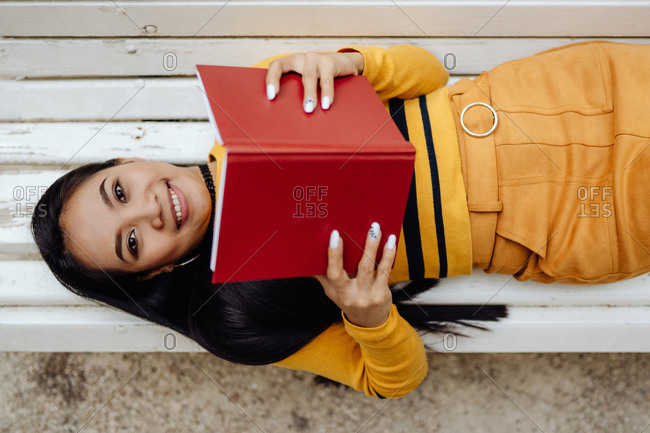 From above of smart brunette Asian woman reading book in red cover lying down on white bench in park