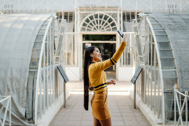 Side view of long haired stylish Asian woman in short skirt smiling and taking selfie on smartphone in glassy architectural sunny hall of building