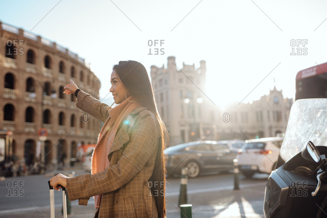 Side view of Asian female with suitcase smiling and stretching out arm while hailing cab on street of tourist city