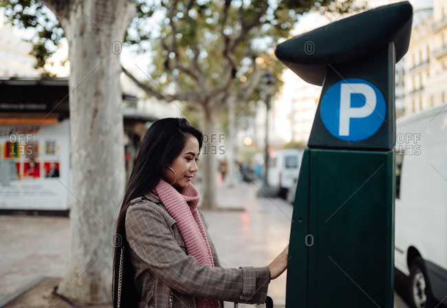 Side view of Asian female in stylish outwear using modern parking machine during trip in city