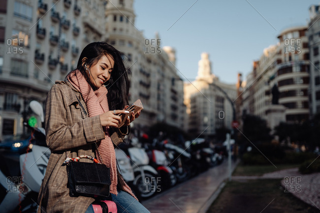 Full length happy Asian woman with smartphone smiling and looking away while sitting on suitcase on sidewalk on city street