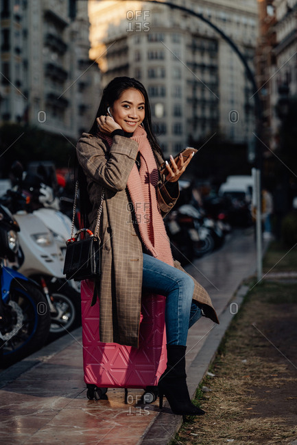 Full length happy Asian woman with smartphone smiling and looking at camera while sitting on suitcase on sidewalk on city street