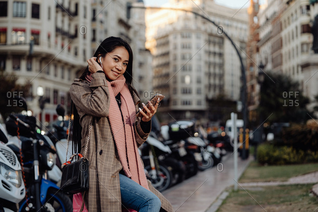 Happy Asian woman with smartphone smiling and looking at camera while sitting on suitcase on sidewalk on city street