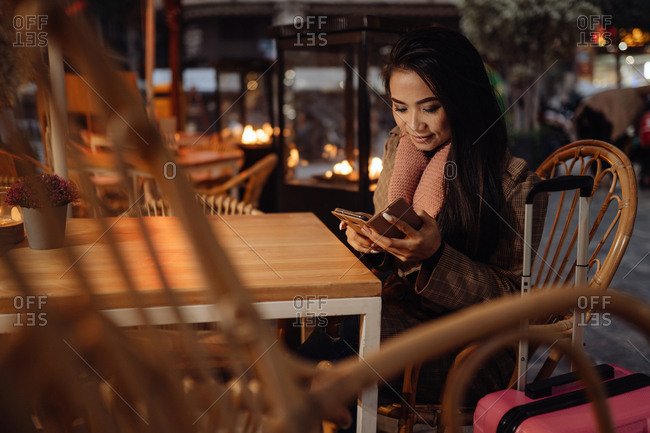 Glad ethnic woman smiling and browsing smartphone while sitting at restaurant table near suitcase in evening on city street