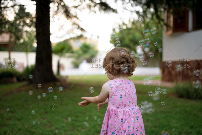 Adorable back view of child in pink dress capturing rainbow soap bubbles on green meadow in park