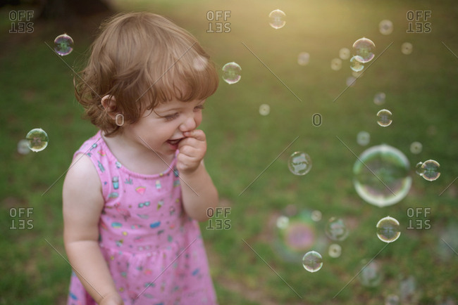 From above adorable child in pink dress laughing and capturing rainbow soap bubbles on green meadow in park