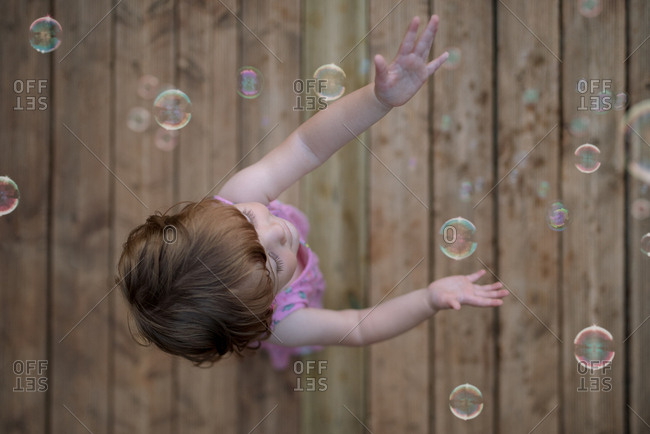 From above adorable child in pink dress laughing and capturing rainbow soap bubbles on wooden ground