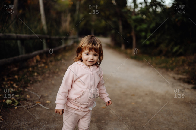 Adorable active kid in warm pink jacket in sunlight in park