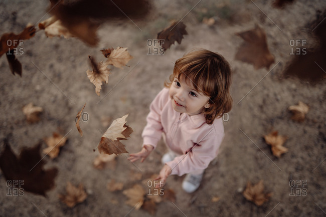 Active playful kid in pink warm clothes throwing up autumn leaves in meadow in park