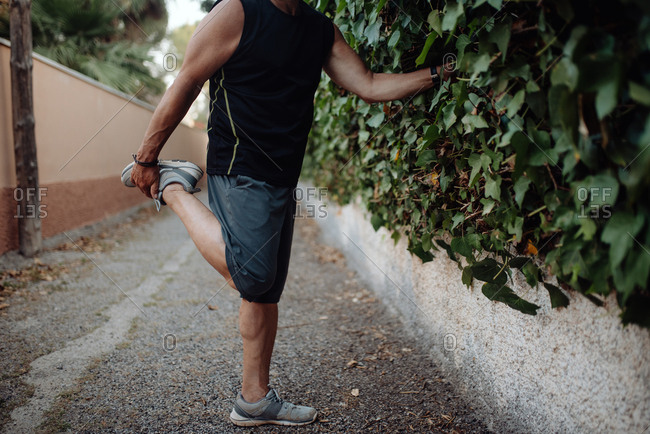 Enthusiastic active mature man in good sportive shape stretching in narrow street along houses and botanical fence in summer day