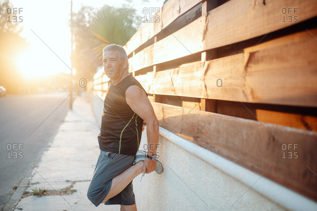Enthusiastic active mature man in good sportive shape stretching in sunny street and wooden fence in summer day