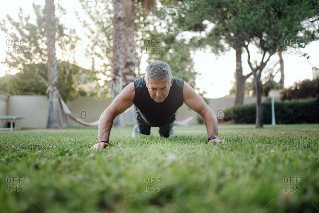 From below strong active mature man in good sportive shape planking and pushing up in green meadow in park in summer day