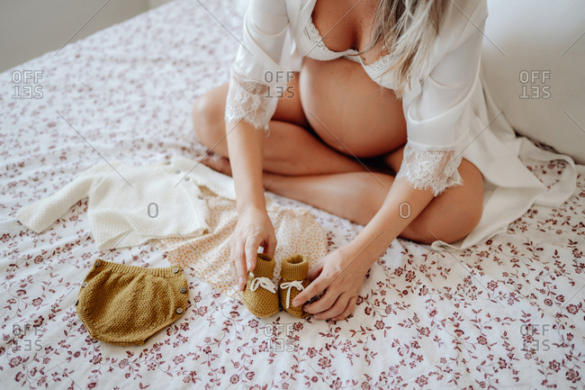 From above crop faceless pregnant female dressed in white open blouse and bra showing clothes for unborn while sitting on bed with crossed legs