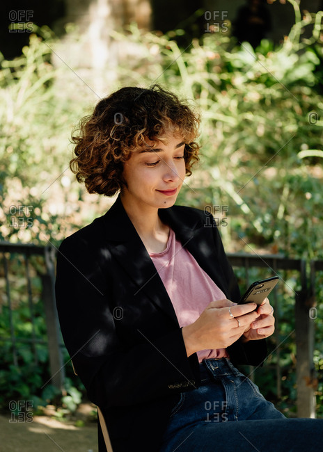 Optimistic woman with curly hair sitting on chair on terrace and browsing smartphone on sunny day in countryside