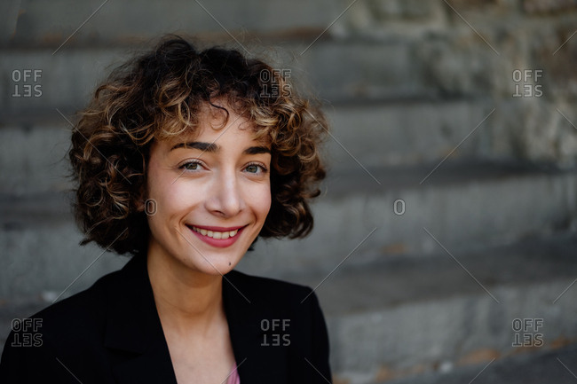 Adult female with curly hair smiling and looking at camera while standing against steps on city street