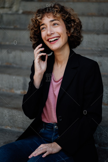 Happy female with curly hair smiling and answering phone call while standing near steps on city street