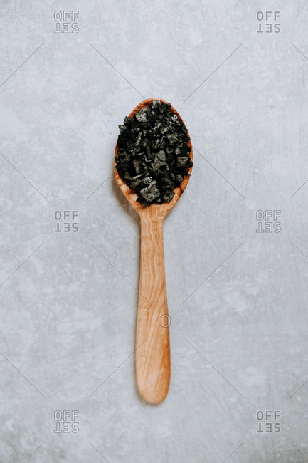 From above wooden spoon with crystals of black salt placed on gray table