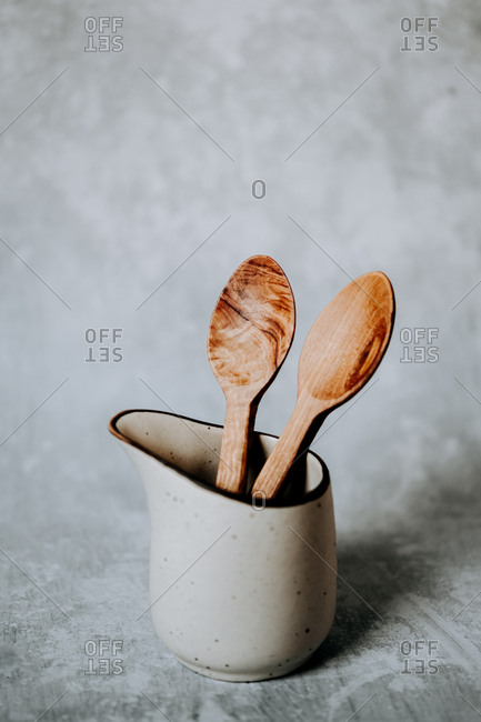 Metal cup with wooden spoons placed against gray wall in kitchen