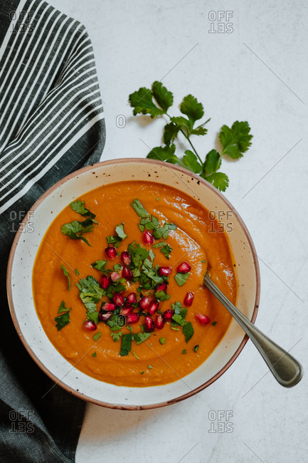 From above bowl of delicious pumpkin cream soup with parsley and pomegranate seeds placed on table