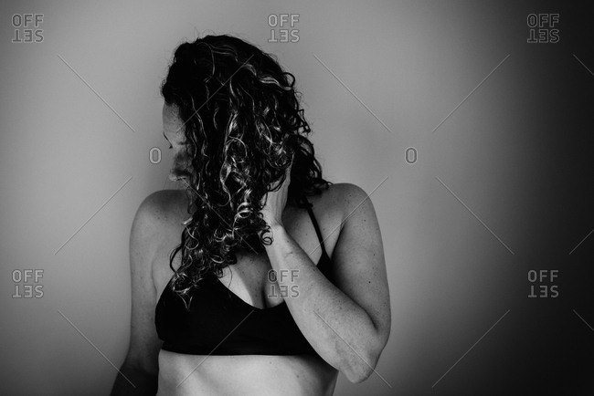 Brunette woman with curly hair looking away