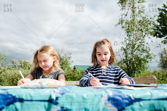 Two little girls making artwork on an outdoor table