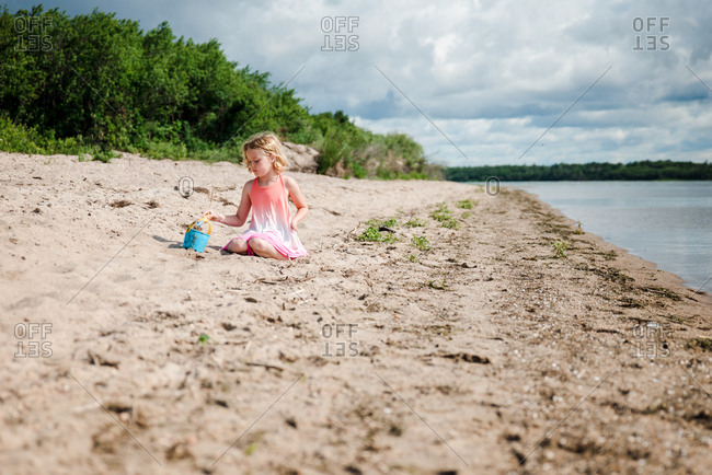 Little girl sitting on beach playing with bucket