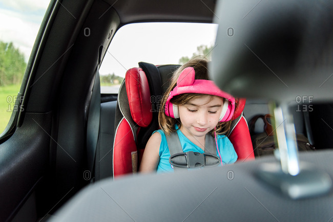 Young girl wearing pink headphones while riding in back seat of car