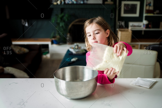 Little girl pouring cake mix into a bowl