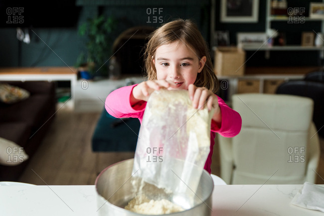 Little girl dumping cake mix into a bowl