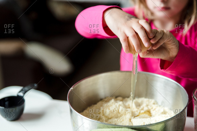 Little girl adding eggs into a cake mix