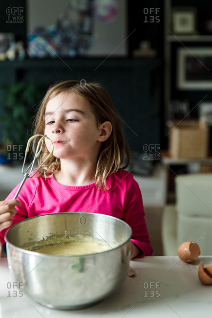 Little girl licking the whisk after mixing cake ingredients