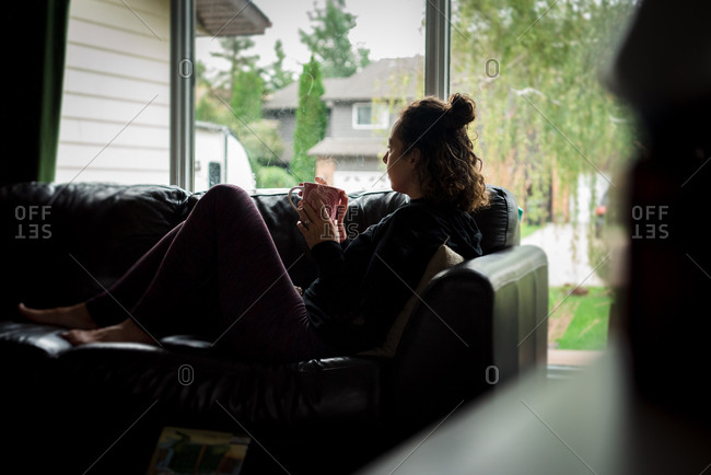 Brunette woman relaxing on sofa with cup of coffee and looking out window