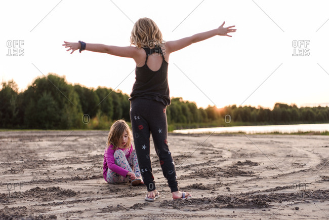 Two girls playing on beach at sunset