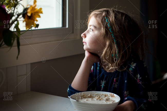 Young girl eating breakfast and gazing out window