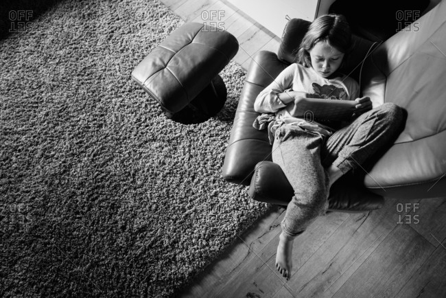Overhead view of a young girl playing on tablet in black and white