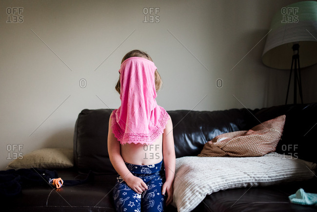 Little girl getting dressed with pink shirt on her head