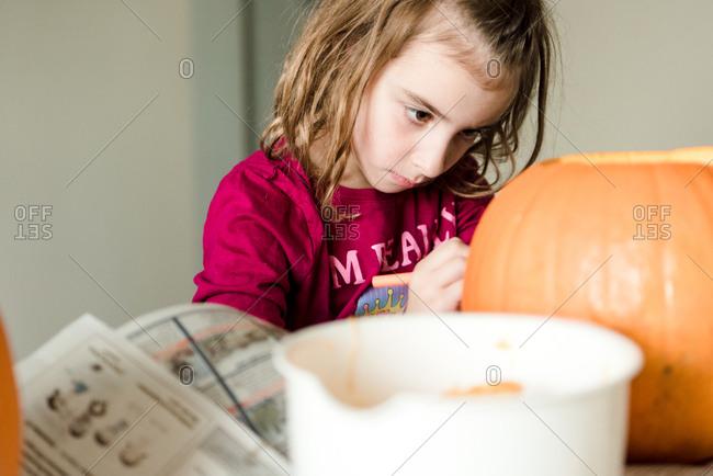 Little girl carving a pumpkin for Halloween