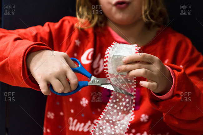 Young girl cutting ribbon while decorating for Christmas